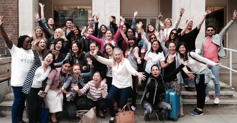 Group shot of postgraduates cheering on steps after taking their exam