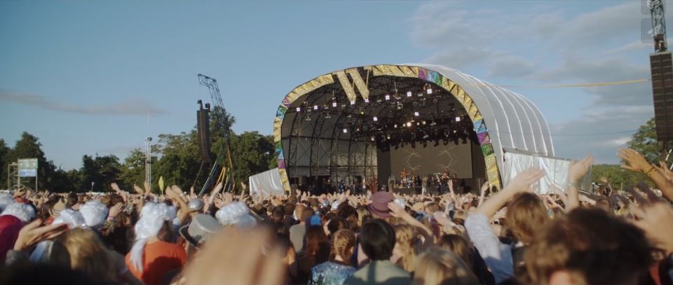 Long shot of crowds and performers on stage at Wilderness event